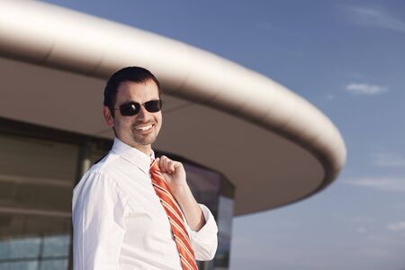 Portrait of smiling young business person in white shirt, orange tie and sunglasses standing in front of office building. Stockfoto