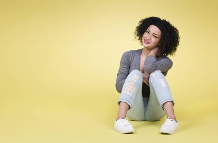 Happy smiling woman sitting on yellow isolated background with empty copy space.