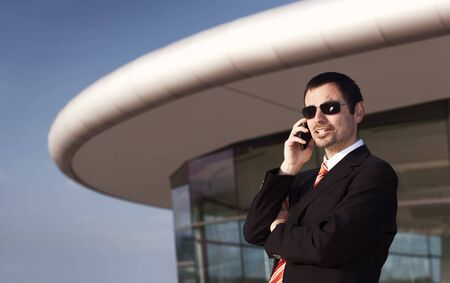 Young business person in black suit and sunglasses talking on mobile phone with office building and blue sky in background. Stockfoto