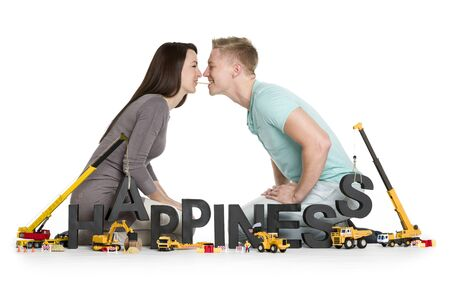 Creating happiness concept: Cheerful young man and woman along with construction machines building the word happiness, isolated on white background.