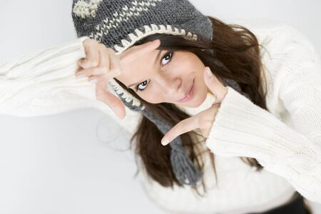 Charming young woman in warm winter clothes, making a photo frame with her hands while looking up and smiling, isolated on grey background. Stockfoto