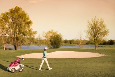 Woman golf player walking during sunset with golf bag at beautiful fairway with lake and bunker in background.