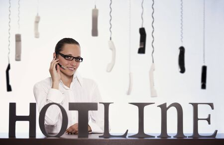 Smiling female phone operator in call centre sitting at desk and talking with headset providing customer support with many phone receivers hanging in background. Stockfoto