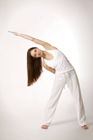 Young lady practicing yoga in triangle posture (Trikonasana) in white clothes on white background, high-key image. Stok Fotoğraf