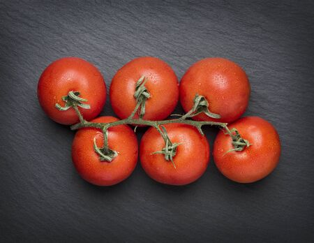 Bunch of fresh tomatoes isolated on dark grey stone slab background. 스톡 콘텐츠