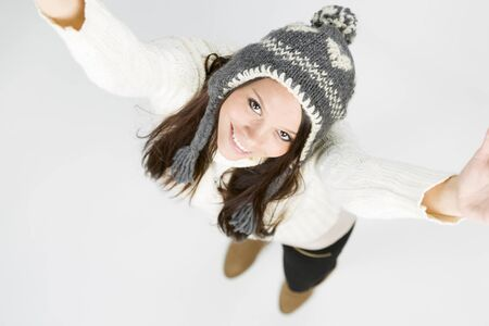 Sweet young girl in warm winter sweater and grey cap, looking up with raised arms and cute smile, isolated on grey background. Stockfoto