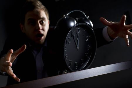 Young desperate business person in dark suit at office desk reaching alarm clock showing five minutes to twelve o'clock and trying to rescue his business, low-key image.