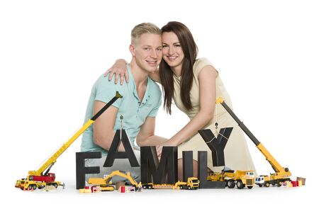 Start family concept: Happy smiling man and woman hugging along with construction machines building the word family, isolated on white background. Stockfoto