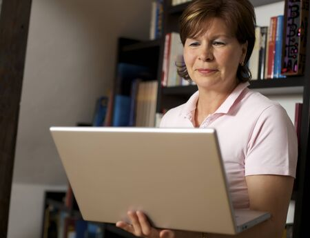 Friendly senior woman standing in front of bookshelf and holding a laptop. Stock Photo