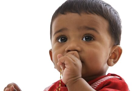 Portrait of sweet indian baby in red clothes looking straight.