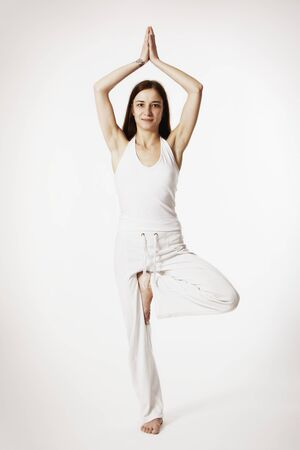 Young lady practicing yoga in tree posture (Vrikshasana) in white clothes on white background, high-key image. Stockfoto