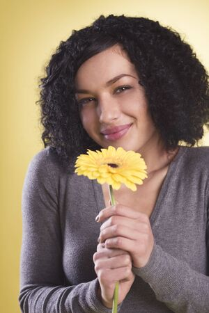 Beautiful girl being happy smelling a yellow blossom. Stockfoto