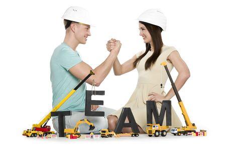 Forming a team: Joyful man and woman building team-word. Stok Fotoğraf