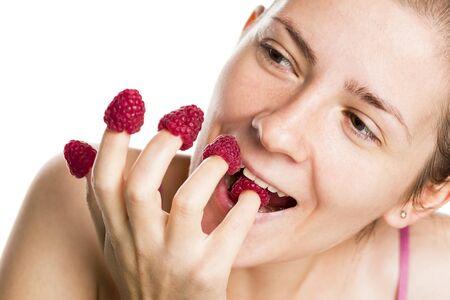 Joyous girl eating raspberries from fingers. Stok Fotoğraf