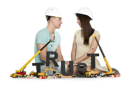 Establishing trust: Young couple with machines building trust-word. Imagens