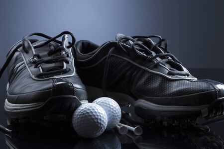 Golf balls, tees and shoes isolated on dark blue background. 写真素材