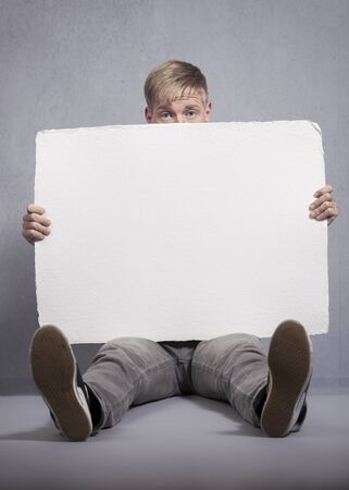Upsetting news: Unhappy man presenting white blank signboard with space for text isolated on grey background. Фото со стока