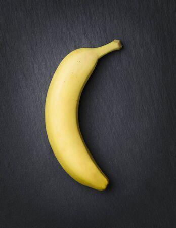 Yellow banana isolated on a dark stone slab.