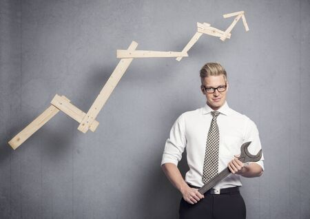 Concept: Building your own successful career or business. Young confident businessman holding wrench in front of business graph with positive trend, isolated on grey background. Imagens