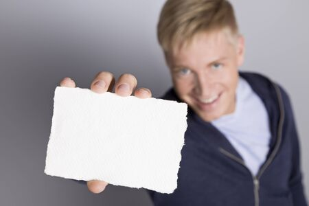Great idea: Joyous man showing blank white card with space for text isolated on grey background, top view.