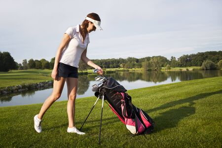 Woman golf player taking out golf club from golf bag on golf course with beautiful pond and trees in background. Stockfoto