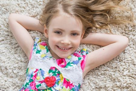 Eine fröhliche kleine Mädchen mit lustigen Schwänze liegt auf dem weißen Teppich. Isoliert auf dem weißen Hintergrund Standard-Bild