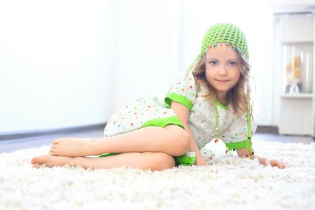 white carpet: Cute girl wearing a green hat on a furry white carpet Stock Photo