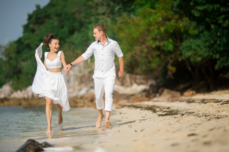 prime adult: Caucasian prime adult male groom and female bride running barefoot on beach.