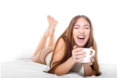 Attractive woman with a white cup of coffee on the bed. White concept. Laughing from ear to ear.