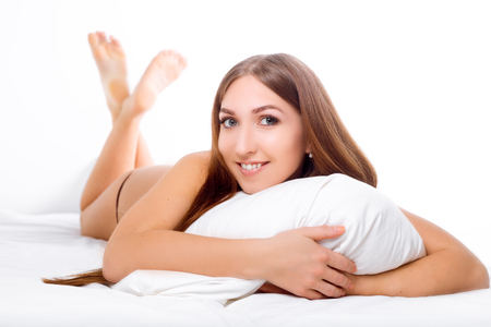 The woman lies on the edge of the bed and smiling , with her head resting on the pillow . The hands are under the pillow. Fashion consept. Stock Photo