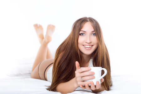 home comforts: Attractive woman with a cup of coffee on the bed. White concept. Stock Photo