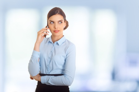 phon: Business woman standing against office window talking on mobile phone. Blue background. Stock Photo