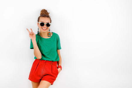 red shorts: beautiful woman in sunglasses wearing in red shorts and green T-shirt standing near white wall, smiling and shows victory, fashion concept
