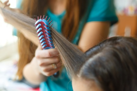 Closeup hairdresser coiffeur makes hairstyle. Blue comb.