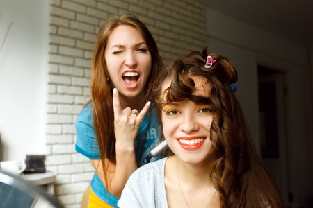 Two young women having fun and smiling . Preparing for a party. Hairdresser and young woman laughing and making fun.