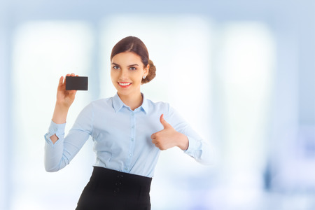 copyspase: Portrait of happy smiling young beautiful businesswoman showing something on card or blank copyspase for product or sign text, making thumb up and saying Ok. Blue background.