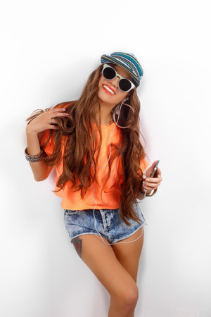 vibrance: beautiful woman in sunglasses wearing in black hat and orange T-shirt listening music near white wall, holding a cell phone in hand, fashion concept