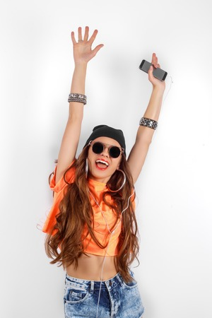 vibrance: beautiful woman in sunglasses wearing in black hat and orange T-shirt listening music and dancing near white wall, holding a cell phone in hand, hands raised up, fashion concept Stock Photo