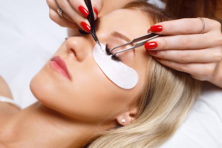 Eyelash Extension Procedure. Woman Eye with Long Eyelashes. Lashes. Close up, selected focus.