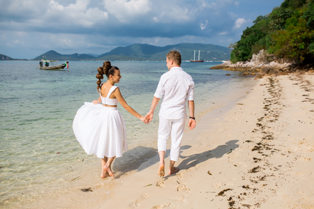 Caucasian prime adult male groom and female bride walking barefoot on beach. Stock Photo