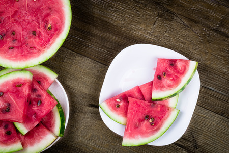 triangle shaped: Triangle shaped watermelon slices placed in ceramic bowl on dark grungy background, top view Stock Photo