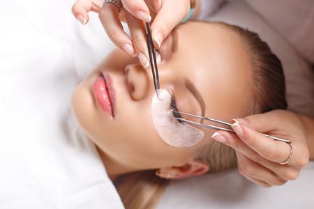 pinzas: Procedimiento de extensión de pestañas. Mujer de los ojos con las pestañas largas. Latigazos. De cerca, enfoque seleccionado.