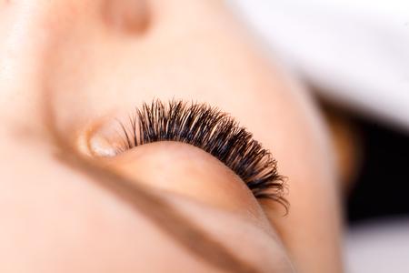 pinzas: Procedimiento de extensión de pestañas. Mujer de los ojos con las pestañas largas. Latigazos. De cerca, enfoque selectivo macro Foto de archivo