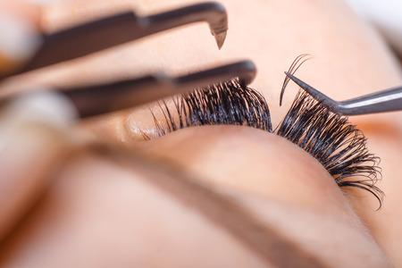 falso: Procedimiento de extensión de pestañas. Mujer de los ojos con las pestañas largas. Latigazos. De cerca, enfoque selectivo macro Foto de archivo
