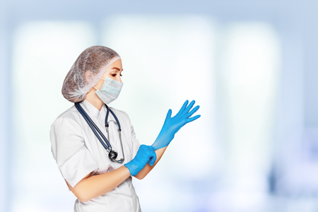 medico: Medical surgeon doctor woman over blue clinic background. Doctor putting on sterile gloves. Place for medical advertise, medical advertising concept.