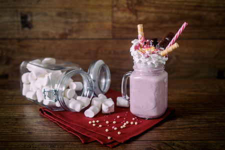 raspberry jelly: Glass jar of homemade raspberry smoothie cocktail, served with whipped cream, caramel jelly beans and wafer rolls over old dark wood background with jar of marshmallow over background.