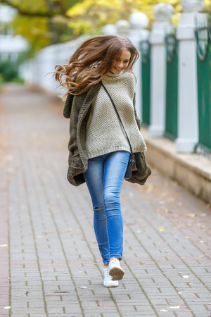 cardigan: Beautiful young woman in knitted cardigan with a hood walking in autumn park