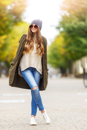 Beautiful young woman in knitted cardigan with a hood walking in autumn park