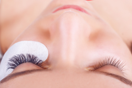 focus on: Eyelash Extension Procedure. Woman Eye with Long Eyelashes. Lashes. Close up, selected focus.