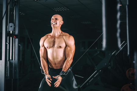crossover: Bodybuider demonstrate crossover exercises in the gym